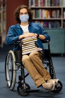 Menino em cadeira de rodas segurando um monte de livros