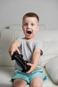 Menino em casa brincando com joystick