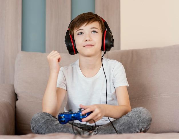 Menino em casa jogando