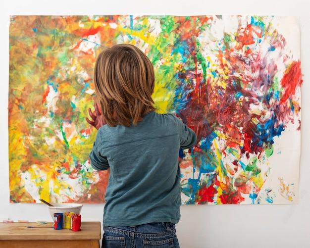 Menino em casa pintando