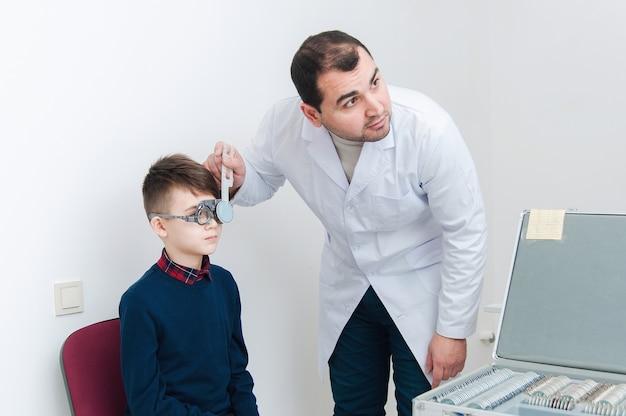 Menino em exame oftalmológico por oftalmologista