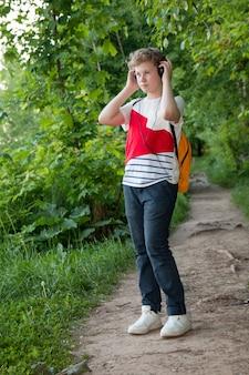Menino em fones de ouvido escuta música. adolescente em fones de ouvido na floresta
