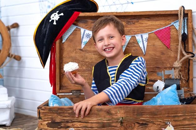 Menino em forma de piratas no leme.
