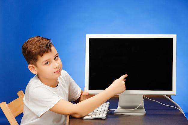 Menino em idade escolar, sentado com o laptop monitor no estúdio