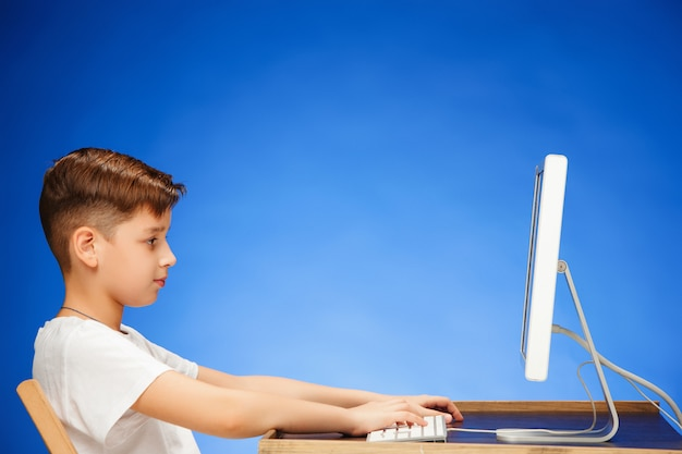 Menino em idade escolar, sentado na frente do laptop monitor
