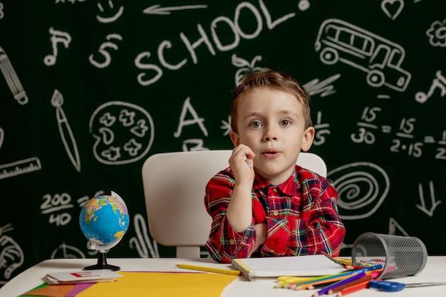 Menino em idade pré-escolar fazendo dever de casa