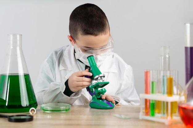 Menino em laboratório com microscópio