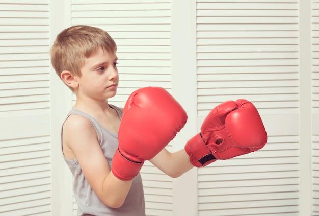 Menino em luvas de boxe vermelhas. conceito de esporte