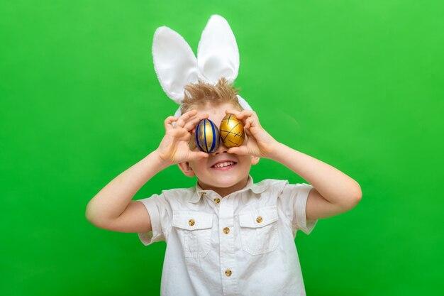 Menino em orelhas de coelho coelho na cabeça segurando ovos de páscoa nos olhos em verde