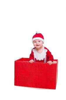 Menino em pé em uma enorme caixa de presente de natal