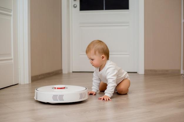 Menino em roupas brancas com um aspirador de pó robótico no chão da casa