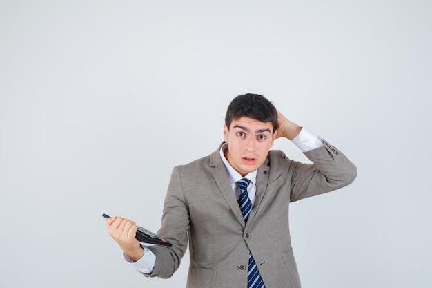 Menino em terno formal segurando calculadora, coçando a cabeça e olhando pensativo, vista frontal.