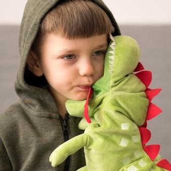 Menino em traje de dinossauro com brinquedo