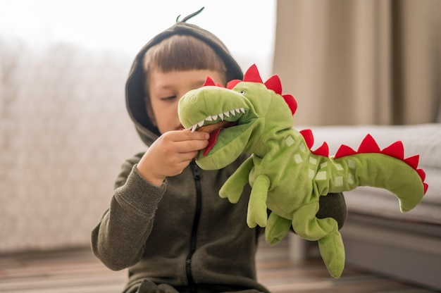 Menino em traje de dinossauro, jogando em casa