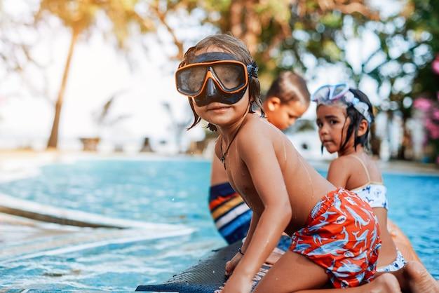 Menino em trajes de banho e óculos de proteção nadando em uma piscina com seus amiguinhos em um barco inflável.