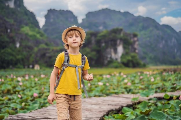 Menino em um amarelo no caminho entre o lago de lótus mua caverna ninh binh vietnã vietnã reabre após