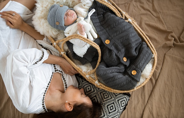 Menino em um berço de vime com um brinquedo no fundo de um cobertor. conceito de família feliz.