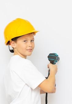 Menino em um capacete com uma chave de fenda