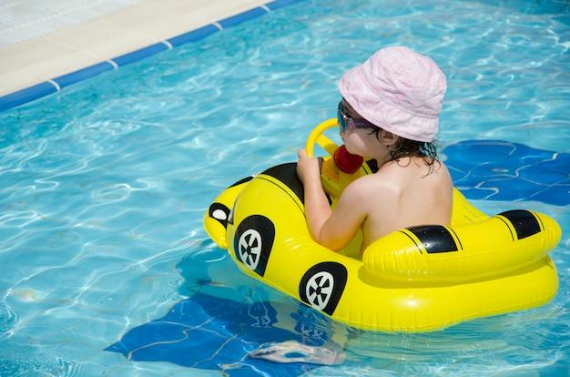 Menino em um carro amarelo inflável na piscina
