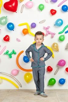 Menino em um fundo branco com balões coloridos menino de pijama em um fundo branco com balões