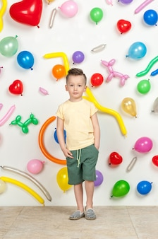 Menino em um fundo branco com balões coloridos menino em um top e shorts
