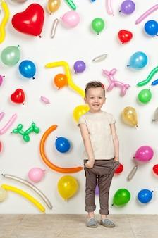 Menino em um fundo branco com balões coloridos menino em uma blusa e calça