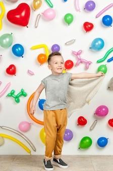 Menino em um fundo branco com balões coloridos menino em uma camiseta sem mangas e calças em um fundo branco