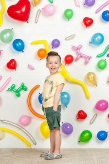 Menino em um fundo branco com balões coloridos menino em uma camiseta sem mangas e shorts em um fundo branco