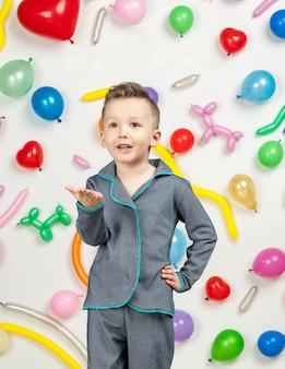 Menino em um fundo branco com balões coloridos menino mandando um beijo no ar