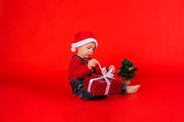 Menino em um macacão jeans e um chapéu de natal com uma pequena árvore de natal sentado