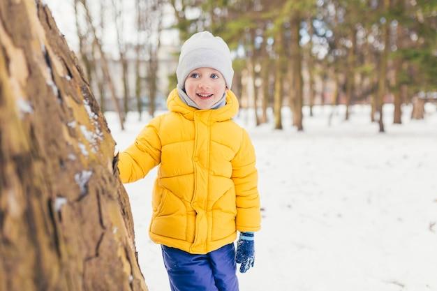 Menino em um passeio no parque com a família no inverno, se divertindo e curtindo a neve