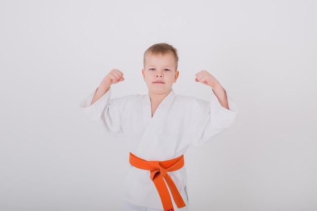 Menino em um quimono branco com as mãos levantadas em uma parede branca