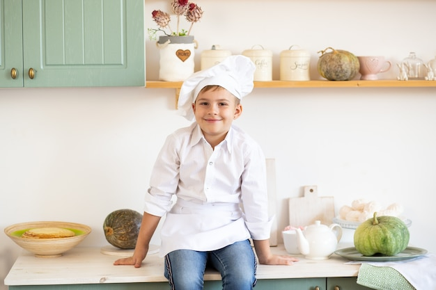 Menino em um toque de chefs sentado em um balcão da cozinha