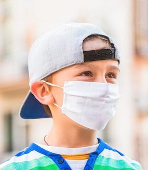 Menino em uma bandagem cirúrgica. rapaz com uma máscara médica. quarentena e vírus de proteção. quarentena do coronavírus.