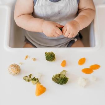 Menino em uma cadeira alta comendo vegetais sozinho