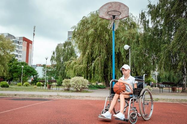 Menino em uma cadeira de rodas na quadra de basquete. reabilitação, pessoa com deficiência, criança paralítica, feliz com deficiência.