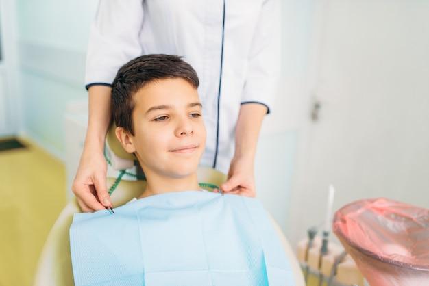 Menino em uma cadeira odontológica, odontopediatria