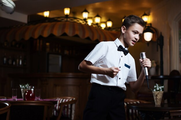 Menino em uma camisa branca que canta no microfone em um restaurante.