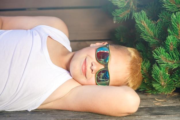 Menino em uma camiseta branca e óculos pretos deitado em um banco no parque