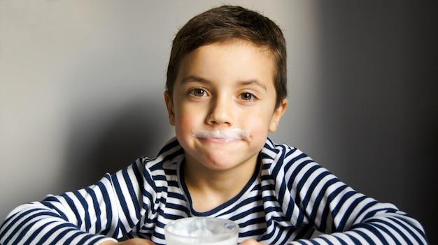 Menino em uma camiseta listrada com um bigode de kefir ou leite com um copo na mão