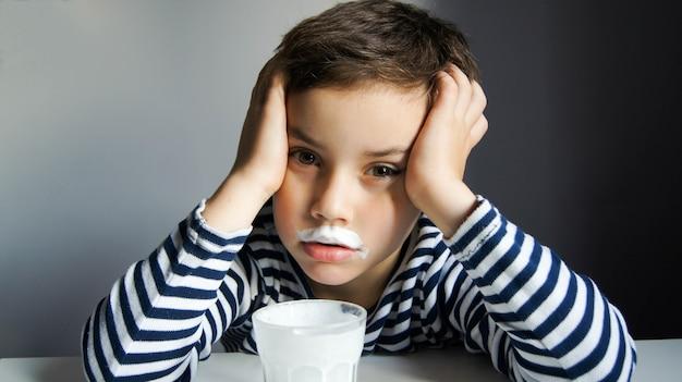 Menino em uma camiseta listrada com um bigode de kefir ou leite ou iogurte com um copo na mão