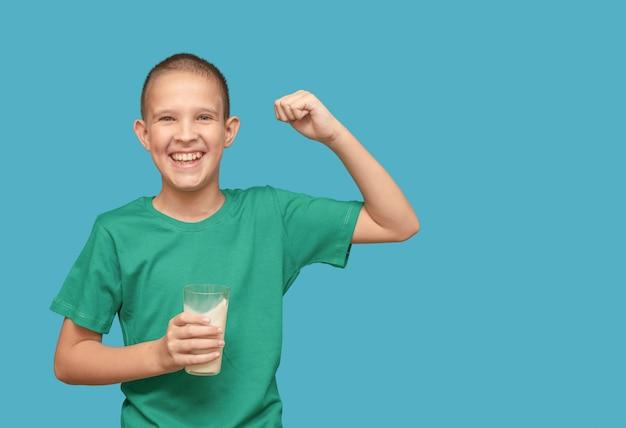Menino em uma camiseta verde com um copo de leite sorriso feliz sobre um fundo azul.