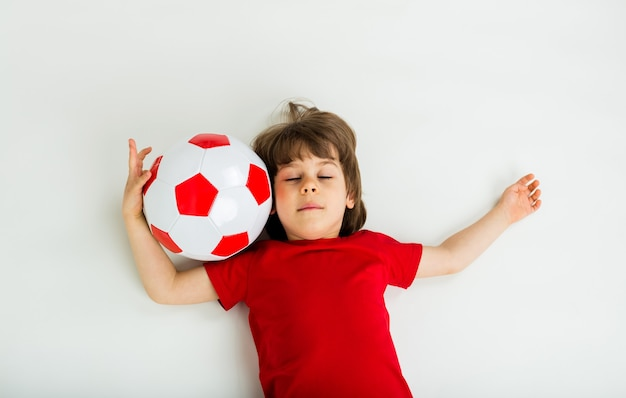 Menino em uma camiseta vermelha encontra-se com os olhos fechados com uma bola de futebol vermelha e branca em uma superfície branca com espaço para texto. esportes para crianças