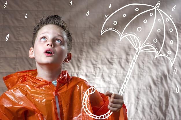Menino em uma capa de chuva laranja e com um guarda-chuva pintado fica na chuva