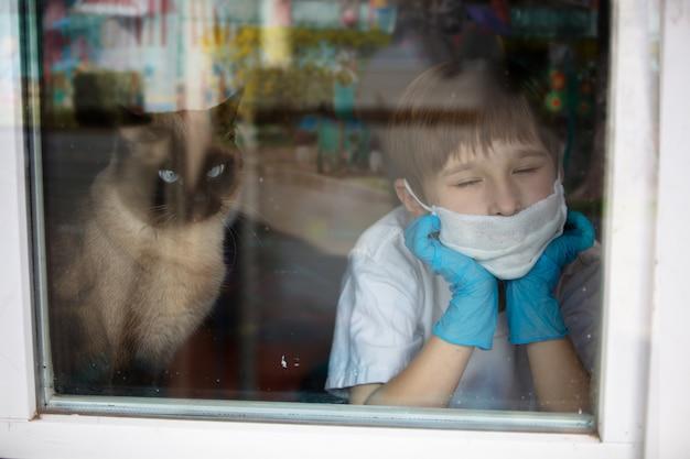 Menino em uma máscara e luvas médicas, olhando pela janela com um gato
