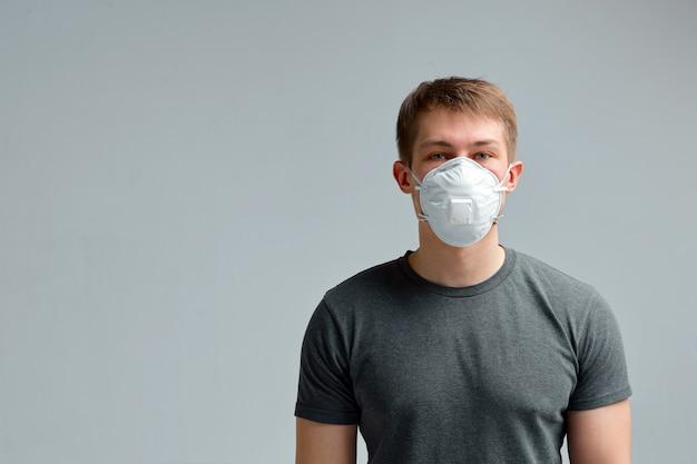 Menino em uma máscara médica, em uma camiseta preta