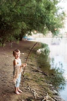 Menino em uma praia de areia com uma vara de pescar