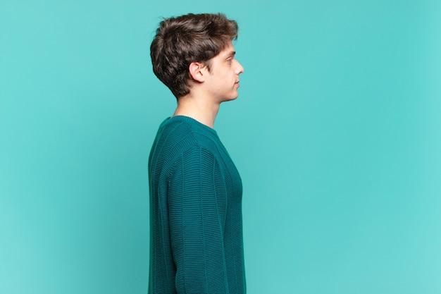 Menino em vista de perfil olhando para copiar o espaço à frente, pensando, imaginando ou sonhando acordado
