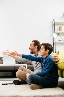 Menino emocional e seu pai feliz sentados no chão com pipoca e gesticulando enquanto assistem a jogos esportivos