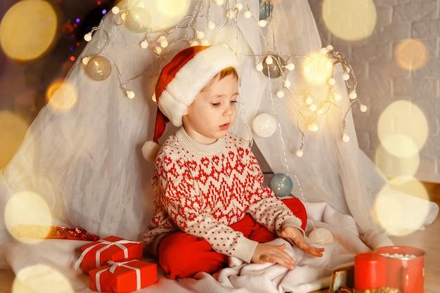 Menino encantador brincando com presentes no chão dentro de casa no dia de natal